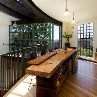 Foto på ett mellanstort funkis linjärt kök och matrum, med träbänkskiva, vita vitvaror, en köksö, en undermonterad diskho, släta luckor, bambugolv och brunt golv