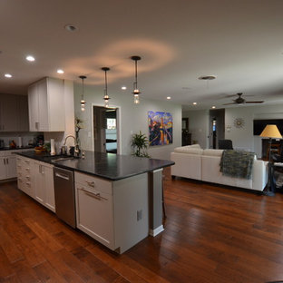 Example of a large trendy l-shaped medium tone wood floor open concept kitchen design in Austin with an undermount sink, flat-panel cabinets, gray cabinets, soapstone countertops, white backsplash, ceramic backsplash, stainless steel appliances and an island