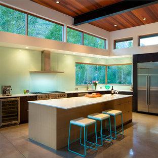 デンバーの中くらいのコンテンポラリースタイルのおしゃれなキッチン (アンダーカウンターシンク、フラットパネル扉のキャビネット、黒いキャビネット、青いキッチンパネル、石スラブのキッチンパネル、シルバーの調理設備、コンクリートの床) の写真