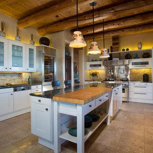 アルバカーキの大きいサンタフェスタイルのおしゃれなキッチン (エプロンフロントシンク、シェーカースタイル扉のキャビネット、白いキャビネット、ベージュキッチンパネル、シルバーの調理設備の、御影石カウンター、石タイルのキッチンパネル、セラミックタイルの床、ベージュの床) の写真