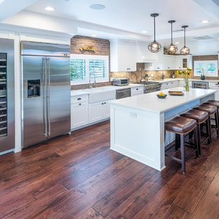 Photo of a mid-sized contemporary l-shaped eat-in kitchen in Los Angeles with a farmhouse sink, shaker cabinets, white cabinets, quartz benchtops, red splashback, brick splashback, stainless steel appliances, dark hardwood floors and with island.