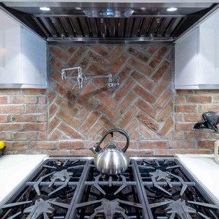 ロサンゼルスの中サイズのコンテンポラリースタイルのおしゃれなキッチン (エプロンフロントシンク、シェーカースタイル扉のキャビネット、白いキャビネット、クオーツストーンカウンター、赤いキッチンパネル、レンガのキッチンパネル、シルバーの調理設備の、濃色無垢フローリング) の写真