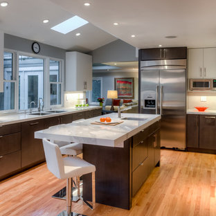 Trendy u-shaped light wood floor kitchen photo in San Francisco with an undermount sink, flat-panel cabinets, dark wood cabinets, white backsplash, stainless steel appliances, marble countertops and an island