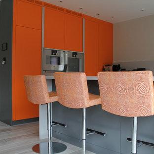 Offene, Große Moderne Küche in L-Form mit flächenbündigen Schrankfronten, orangefarbenen Schränken, Küchenrückwand in Grau, Glasrückwand, Küchengeräten aus Edelstahl, Porzellan-Bodenfliesen und Kücheninsel in Kent