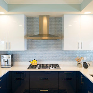 Small contemporary u-shaped open plan kitchen in Miami with flat-panel cabinets, quartz benchtops, blue splashback, stainless steel appliances, no island, an undermount sink, blue cabinets, glass tile splashback, laminate floors and beige floor.