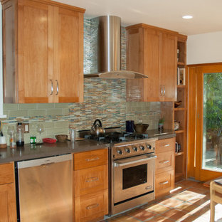 This is an example of a mid-sized transitional l-shaped separate kitchen in San Francisco with shaker cabinets, light wood cabinets, green splashback, ceramic splashback, stainless steel appliances, terra-cotta floors, no island, concrete benchtops, orange floor and grey benchtop.