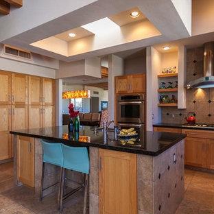 フェニックスの大きいサンタフェスタイルのおしゃれなキッチン (アンダーカウンターシンク、シェーカースタイル扉のキャビネット、中間色木目調キャビネット、御影石カウンター、茶色いキッチンパネル、磁器タイルのキッチンパネル、シルバーの調理設備の、ライムストーンの床、ベージュの床、黒いキッチンカウンター) の写真