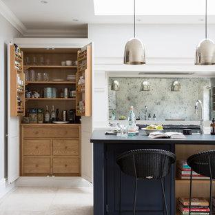 エセックスの中くらいのトランジショナルスタイルのおしゃれなアイランドキッチン (ベージュの床、ミラータイルのキッチンパネル、トラバーチンの床) の写真