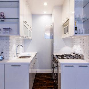На фото: маленькая параллельная кухня в современном стиле с обеденным столом, врезной раковиной, плоскими фасадами, белыми фасадами, столешницей из кварцевого агломерата, белым фартуком, фартуком из плитки мозаики, техникой из нержавеющей стали и темным паркетным полом с