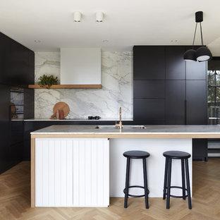 Offene Moderne Küche in L-Form mit Unterbauwaschbecken, schwarzen Schränken, Marmor-Arbeitsplatte, Küchenrückwand in Weiß, Rückwand aus Marmor, schwarzen Elektrogeräten, hellem Holzboden, Kücheninsel und weißer Arbeitsplatte in Adelaide