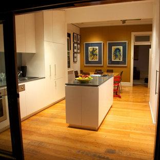 Zweizeilige, Kleine Moderne Wohnküche mit Doppelwaschbecken, flächenbündigen Schrankfronten, weißen Schränken, Quarzwerkstein-Arbeitsplatte, Küchenrückwand in Grau, Glasrückwand, Küchengeräten aus Edelstahl, hellem Holzboden, Kücheninsel, braunem Boden und grauer Arbeitsplatte in Sydney