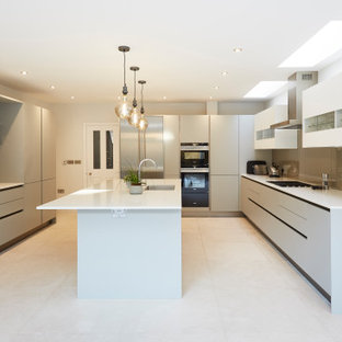 Inspiration for a large contemporary u-shaped kitchen in London with an integrated sink, flat-panel cabinets, grey cabinets, grey splashback, glass sheet splashback, integrated appliances, porcelain flooring, an island, white floors and white worktops.