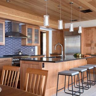 Foto de cocina comedor rústica con fregadero de un seno, puertas de armario de madera oscura, electrodomésticos de acero inoxidable, suelo de madera clara, una isla y suelo beige