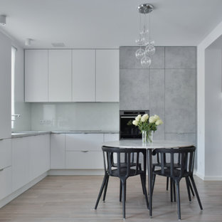 Mid-sized scandinavian eat-in kitchen pictures - Example of a mid-sized danish l-shaped ceramic floor and brown floor eat-in kitchen design in Stockholm with a single-bowl sink, flat-panel cabinets, white cabinets, laminate countertops, white backsplash, glass sheet backsplash, no island, gray countertops and paneled appliances
