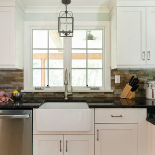 This is an example of a traditional kitchen in Raleigh with a farmhouse sink, white cabinets and slate splashback.
