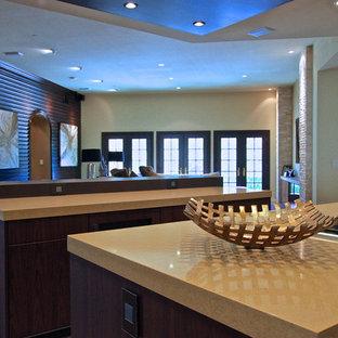 オレンジカウンティの大きいコンテンポラリースタイルのおしゃれなキッチン (フラットパネル扉のキャビネット、茶色いキャビネット、クオーツストーンカウンター、パネルと同色の調理設備、磁器タイルの床、アンダーカウンターシンク、黄色いキッチンパネル、ガラスタイルのキッチンパネル) の写真