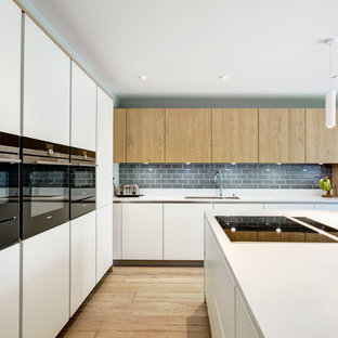 Inspiration for a medium sized contemporary l-shaped open plan kitchen in Berkshire with flat-panel cabinets, white cabinets, composite countertops, grey splashback, metro tiled splashback, light hardwood flooring, an island, black appliances, brown floors and a double-bowl sink.