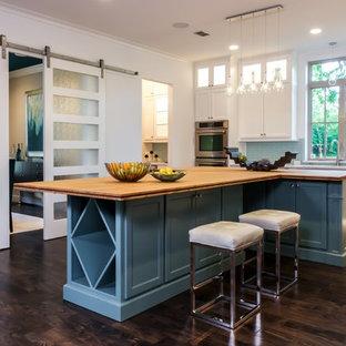 Klassisk inredning av ett kök, med en undermonterad diskho, skåp i shakerstil, vita skåp, blått stänkskydd, stänkskydd i glaskakel, rostfria vitvaror, mörkt trägolv, flera köksöar och träbänkskiva
