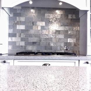 Mittelgroße Moderne Küche mit Schrankfronten mit vertiefter Füllung, weißen Schränken, Arbeitsplatte aus Recyclingglas, Küchenrückwand in Metallic, Rückwand aus Glasfliesen, Kücheninsel und weißer Arbeitsplatte in Miami