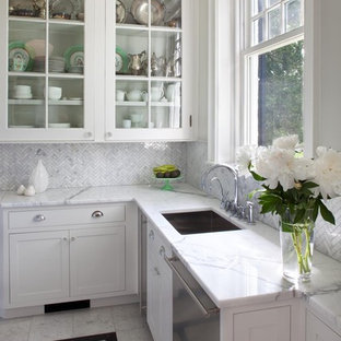 Elegant kitchen photo in Philadelphia with glass-front cabinets, stainless steel appliances, marble countertops, a single-bowl sink, white cabinets, white backsplash and marble backsplash