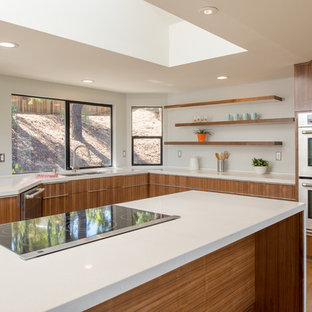 Inspiration for a large contemporary u-shaped medium tone wood floor open concept kitchen remodel in San Diego with an undermount sink, flat-panel cabinets, dark wood cabinets, quartz countertops, white backsplash, stainless steel appliances and an island