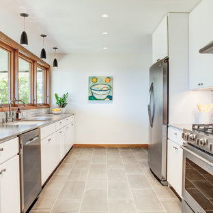 Large contemporary enclosed kitchen ideas - Large trendy galley gray floor and concrete floor enclosed kitchen photo in San Francisco with an undermount sink, flat-panel cabinets, white cabinets, stainless steel countertops, white backsplash, stainless steel appliances, no island, gray countertops and subway tile backsplash