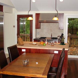 クリーブランドの中サイズのアジアンスタイルのおしゃれなキッチン (シェーカースタイル扉のキャビネット、中間色木目調キャビネット、木材カウンター、シルバーの調理設備の、濃色無垢フローリング、アンダーカウンターシンク、ベージュキッチンパネル、セメントタイルのキッチンパネル) の写真