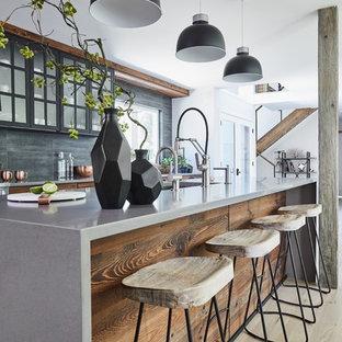 Пример оригинального дизайна: линейная кухня-гостиная среднего размера в стиле модернизм с накладной раковиной, плоскими фасадами, темными деревянными фасадами, столешницей из бетона, черным фартуком, фартуком из каменной плитки, техникой под мебельный фасад, светлым паркетным полом, островом, серым полом и серой столешницей