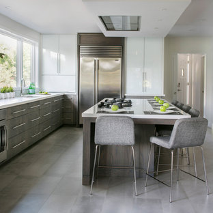 Inspiration for a large contemporary u-shaped porcelain tile kitchen remodel in New York with an undermount sink, flat-panel cabinets, medium tone wood cabinets, quartz countertops, stainless steel appliances and an island