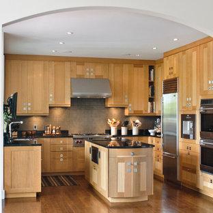 バンクーバーのアジアンスタイルのおしゃれなキッチン (アンダーカウンターシンク、シェーカースタイル扉のキャビネット、中間色木目調キャビネット、御影石カウンター、グレーのキッチンパネル、セラミックタイルのキッチンパネル、シルバーの調理設備の、濃色無垢フローリング) の写真