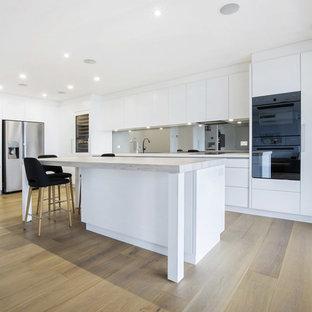 シドニーの大きいモダンスタイルのおしゃれなキッチン (アンダーカウンターシンク、フラットパネル扉のキャビネット、白いキャビネット、クオーツストーンカウンター、メタリックのキッチンパネル、ミラータイルのキッチンパネル、黒い調理設備、淡色無垢フローリング、黄色い床) の写真