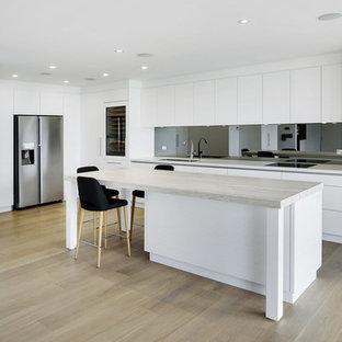 Diseño de cocina en L, moderna, grande, abierta, con fregadero bajoencimera, armarios con paneles lisos, puertas de armario blancas, encimera de cuarzo compacto, salpicadero metalizado, salpicadero con efecto espejo, electrodomésticos negros, suelo de madera clara, una isla y suelo amarillo