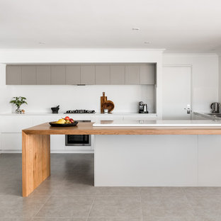 This is an example of a large modern galley kitchen in Perth with a drop-in sink, flat-panel cabinets, white cabinets, quartz benchtops, white splashback, porcelain splashback, stainless steel appliances, porcelain floors, with island and grey floor.