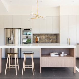 Mid-sized contemporary l-shaped kitchen in Sydney with white cabinets, quartz benchtops, metallic splashback, mosaic tile splashback, stainless steel appliances, slate floors, with island and flat-panel cabinets.