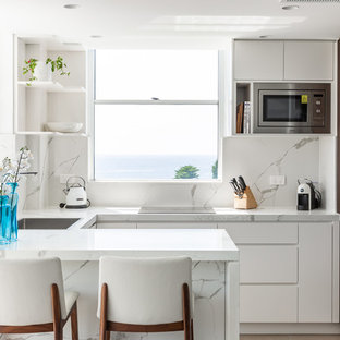 This is an example of a beach style u-shaped kitchen in Sydney with a drop-in sink, flat-panel cabinets, white cabinets, white splashback, stainless steel appliances, beige floor and white benchtop.