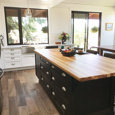 Inspiration for a large farmhouse l-shaped brown floor eat-in kitchen remodel in Vancouver with shaker cabinets, black cabinets, white backsplash, stainless steel appliances, an island, a farmhouse sink, wood countertops, ceramic backsplash and brown countertops