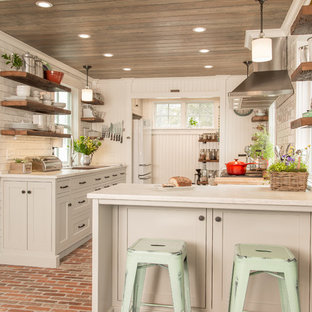 Photo of a country kitchen in Bridgeport with an undermount sink, shaker cabinets, white cabinets, white splashback, subway tile splashback, stainless steel appliances, brick floors, no island, red floor and white benchtop.