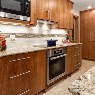 Design ideas for a scandinavian u-shaped eat-in kitchen in Calgary with an undermount sink, flat-panel cabinets, medium wood cabinets, granite benchtops, white splashback, glass tile splashback, stainless steel appliances, porcelain floors and with island.