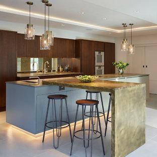 Bild på ett mycket stort funkis kök, med släta luckor, skåp i mörkt trä, en dubbel diskho, bänkskiva i kvartsit, stänkskydd med metallisk yta, spegel som stänkskydd, rostfria vitvaror, klinkergolv i keramik, en köksö och beiget golv