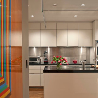Foto på ett avskilt, mellanstort funkis svart u-kök, med släta luckor, vita skåp, stänkskydd med metallisk yta, stänkskydd i metallkakel, en undermonterad diskho, granitbänkskiva, rostfria vitvaror, mellanmörkt trägolv och en köksö