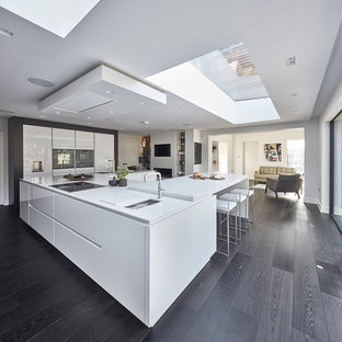 This is an example of a large contemporary u-shaped open plan kitchen in Other with flat-panel cabinets, white cabinets, granite worktops, integrated appliances, dark hardwood flooring, an island and black floors.