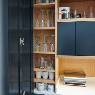 This is an example of a medium sized contemporary u-shaped open plan kitchen in Hertfordshire with shaker cabinets, grey cabinets, quartz worktops, stainless steel appliances, plywood flooring, no island, yellow floors and white worktops.