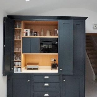 Offene, Mittelgroße Moderne Küche ohne Insel in U-Form mit Schrankfronten im Shaker-Stil, grauen Schränken, Quarzit-Arbeitsplatte, Küchengeräten aus Edelstahl, Sperrholzboden, gelbem Boden und weißer Arbeitsplatte in Hertfordshire