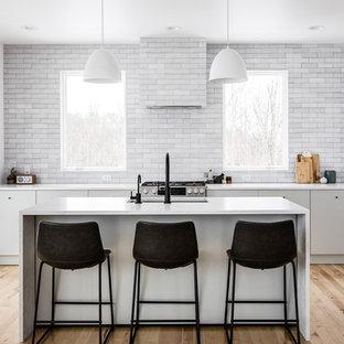 グランドラピッズの広いコンテンポラリースタイルのおしゃれなキッチン (アンダーカウンターシンク、フラットパネル扉のキャビネット、グレーのキャビネット、珪岩カウンター、グレーのキッチンパネル、レンガのキッチンパネル、シルバーの調理設備、淡色無垢フローリング、ベージュの床、白いキッチンカウンター) の写真