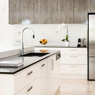 Свежая идея для дизайна: огромная угловая кухня-гостиная в стиле модернизм с врезной раковиной, плоскими фасадами, светлыми деревянными фасадами, столешницей из кварцевого композита, белым фартуком, фартуком из плитки мозаики, черной техникой, мраморным полом, островом и розовым полом - отличное фото интерьера