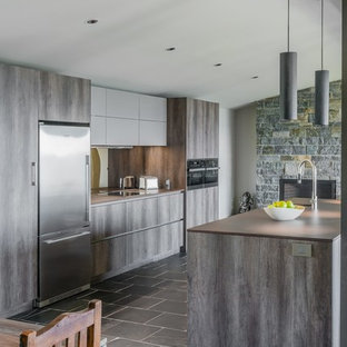 Inspiration for a large eclectic single-wall open plan kitchen in Boston with a farmhouse sink, flat-panel cabinets, dark wood cabinets, granite benchtops, metallic splashback, glass sheet splashback, stainless steel appliances, slate floors, with island, multi-coloured floor and brown benchtop.