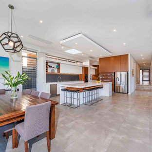 Contemporary l-shaped open plan kitchen in Perth with flat-panel cabinets, white cabinets, black splashback, stainless steel appliances, with island, grey floor and white benchtop.