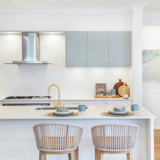 Beach style galley kitchen in Sydney with an undermount sink, flat-panel cabinets, grey cabinets, white splashback, mosaic tile splashback, stainless steel appliances, medium hardwood floors, with island, brown floor and white benchtop.