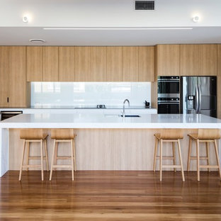 Inspiration for a contemporary galley open plan kitchen in Sunshine Coast with a drop-in sink, flat-panel cabinets, light wood cabinets, white splashback, glass sheet splashback, stainless steel appliances, medium hardwood floors, with island and brown floor.