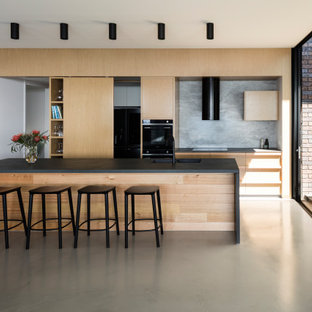 Large contemporary galley kitchen in Sunshine Coast with an undermount sink, flat-panel cabinets, light wood cabinets, grey splashback, black appliances, with island, grey floor and black benchtop.